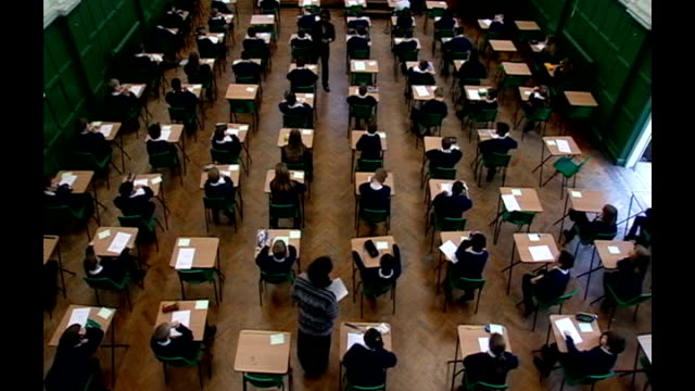 disputed gcse english exam results to stand int anonymous shot of schoolchildren sitting exam - 試験点の映像素材/bロール