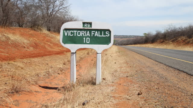 vídeos de stock, filmes e b-roll de a distance sign at the side of the road to victoria falls a large waterfall on the zambezi river at the border of zambia and zimbabwe in southern... - ponto de referência natural