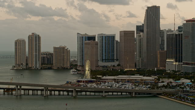 distant aerial view of downtown miami with waterfront, marina, and ferris wheel in the evening. drone-made video with panning camera motion. - macarthur causeway bridge stock videos & royalty-free footage