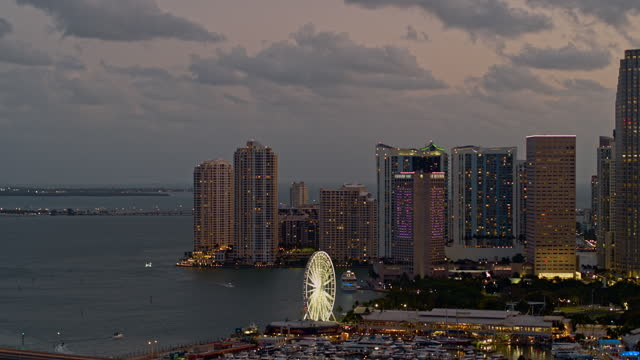 distant aerial view of downtown miami with waterfront, marina, and ferris wheel. drone-made video with panning camera motion. - marina stock videos & royalty-free footage