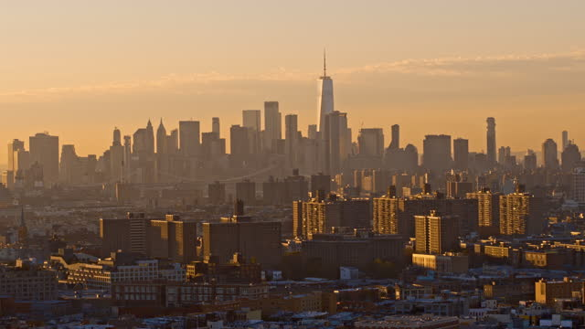 distant aerial view on freedom tower in lower manhattan from bushwick over the residential district in brooklyn, new york, in the evening. drone video with the panning camera motion. - roof stock videos & royalty-free footage