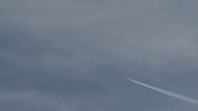 Distant aircraft passes across sky leaving long vapour trail, UK