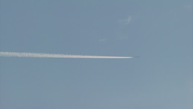 Distant airliner flies from left to right with vapour trail behind, UK