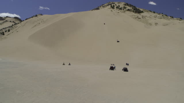distant all-terrain vehicles driving on and climbing sand dune / little sahara, utah, united states - medium group of objects stock videos & royalty-free footage