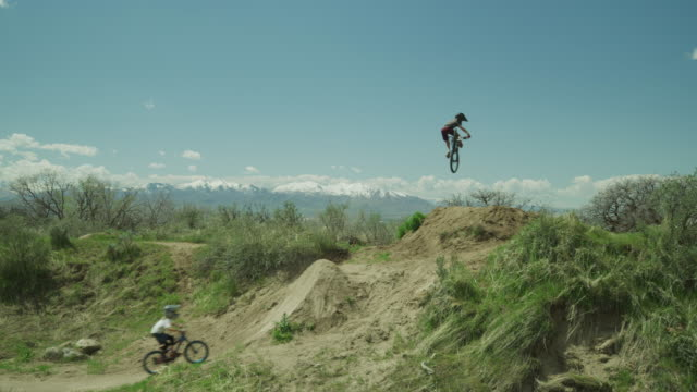 distant boys jumping hill on bicycles at bike park / salt lake city, utah, united states - bmx stock-videos und b-roll-filmmaterial