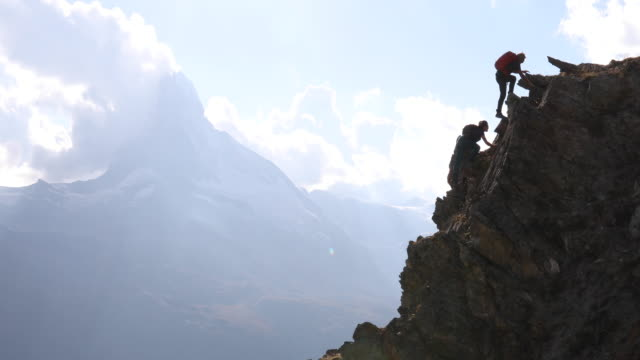 distant climbers ascend steep rock ridge, leader offers assistance - weitwinkelaufnahme stock-videos und b-roll-filmmaterial