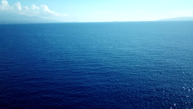 distant clouds hang over horizon and blue ocean expanse - smooth stock videos & royalty-free footage