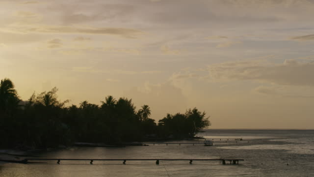 distant docks in ocean at sunset in tahiti / moorea, french polynesia - moorea stock videos and b-roll footage