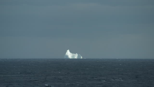 distant iceberg on choppy sea waters - sea passage stock videos and b-roll footage