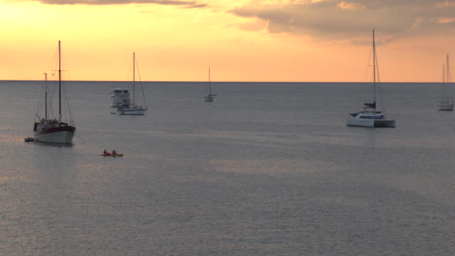 distant kayakers paddle across tranquil sea, between boats - pct stock videos and b-roll footage