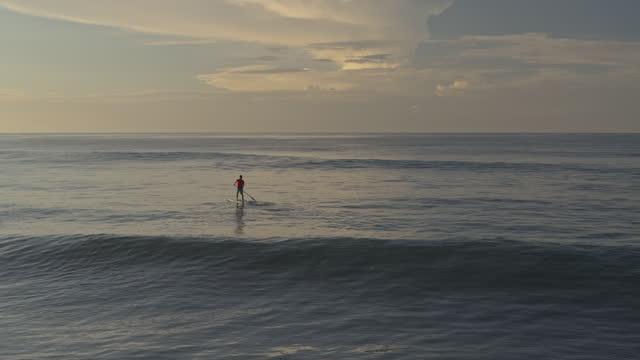 distant man riding stand up paddleboard in ocean waves / san blas, la libertad, el salvador - remo video stock e b–roll