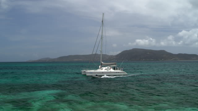 distant motorboat leaving catamaran in ocean near island / st. vincent and the grenadines - 双胴船点の映像素材/bロール