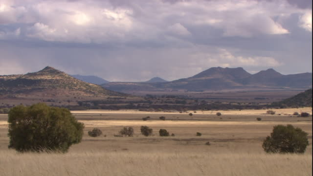distant mountains border a dry valley where storm clouds hover. - bush stock videos & royalty-free footage