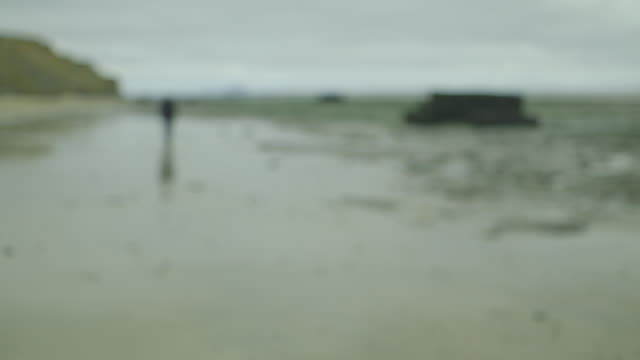 A distant, out-of-focus, figure walks away on a beach in Essex on a cold day, UK.