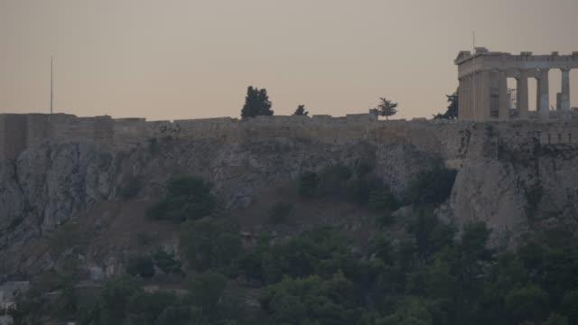 distant panning view of the acropolis before dawn, monastiraki district, athens, greece, europe - acropolis athens stock videos & royalty-free footage