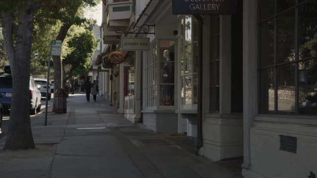 distant people walking on quiet city sidewalk near storefronts / carmel, california, united states - carmel california stock videos & royalty-free footage