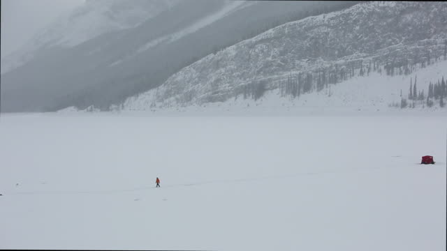 distant person crosses frozen lake to ice fishing shack, mountains - shack stock videos and b-roll footage