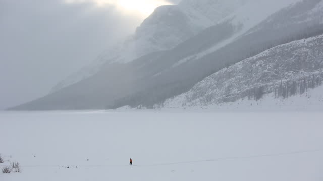 Distant person crosses frozen lake to ice fishing shack, mountains