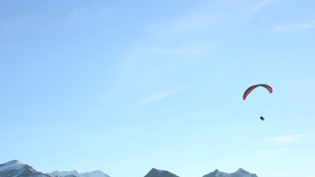 distant person parasails in blue skies, above snowy peaks - paragliding stock videos & royalty-free footage