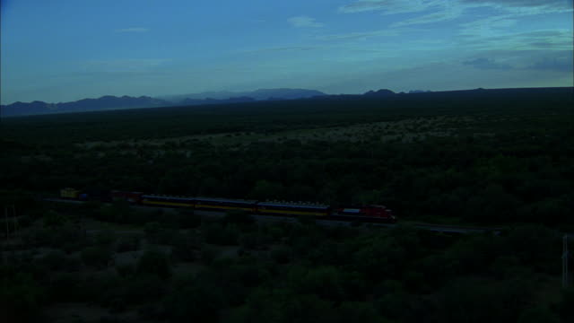 AERIAL Distant rain shower with night falling, and train moving on tracks through scrub desert