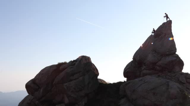 vidéos et rushes de câble de bobine de grimpeurs de roche lointain sur sommet de pinnacle - découverte
