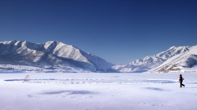 A distant scenic shot of an iced over pond surrounded by snow covered mountains and the sun glistening over the top.  A person walks onto the shot and across to step onto the pond.