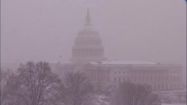 Distant shot of the Capitol dome amid heavy snow while members of Congress inside finalized negotiations on a six month omnibus spending bill to...