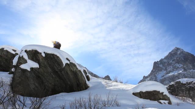 vídeos y material grabado en eventos de stock de distant skier approaches ridge crest, stands in front of sun - vacaciones en la nieve