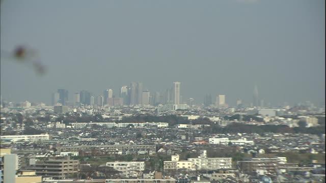 distant skyscrapers in shinjuku fukutoshin extend above surrounding buildings in kanagawa, japan. - 神奈川県点の映像素材/bロール