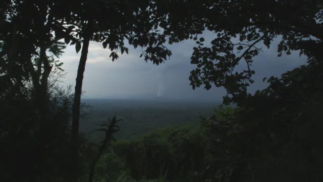 vídeos y material grabado en eventos de stock de distant smoking volcano seen through gap in vegetation, nyamuragira, democratic republic of congo, 2011 - volcán activo