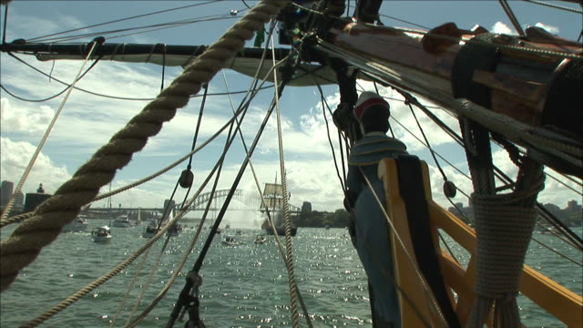 a distant tall ship and sydney harbor are visible under a ship's rigging. - 帆船点の映像素材/bロール