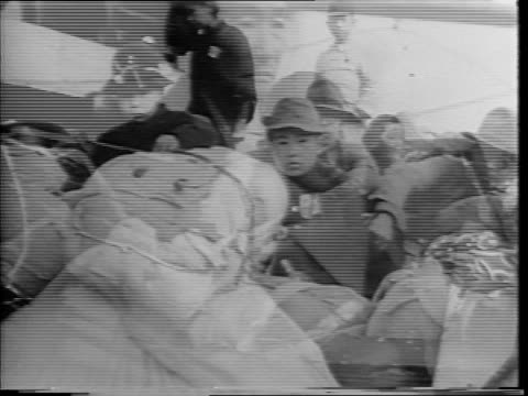 distant view of seoul korea / japanese evacuees sitting with belongings at a port / montage of american soldiers searching people and their... - ワクチン接種点の映像素材/bロール