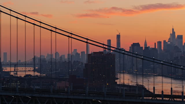 distant view of skyline silhouette includes manhattan midtown and downtown, roosevelt island, ed koch queensboro bridge, and long island city, at sunset over rfk bridge. drone footage with the cinematic wide orbiting-panning camera motion. - panning stock videos & royalty-free footage
