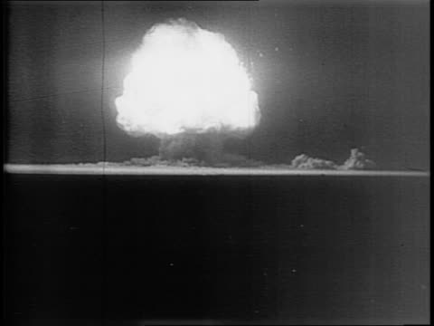 distant view of the atomic bomb impact on desert testing ground / large mushroom cloud moves skyward / the destruction of a steel tower - massenvernichtungswaffe stock-videos und b-roll-filmmaterial