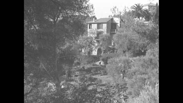 vídeos de stock e filmes b-roll de distant villa lou viei seen through trees / upper room and roof / people, probably journalists, stand at end of gravel road with a semi-circular gate... - 1930