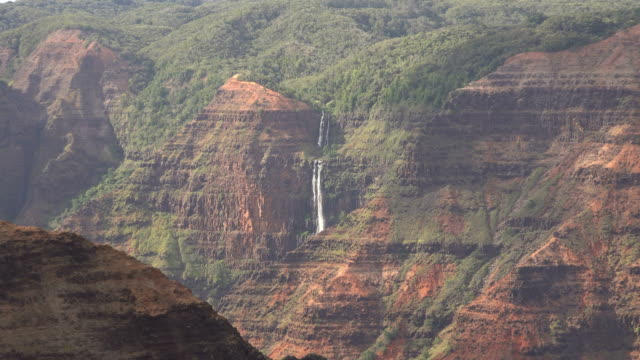 distant waterfall on egde of kauai island mountain range - butte rocky outcrop stock videos & royalty-free footage