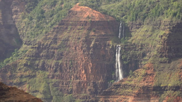 distant waterfalls flowing over edge of kauai island ravine - butte rocky outcrop stock videos & royalty-free footage