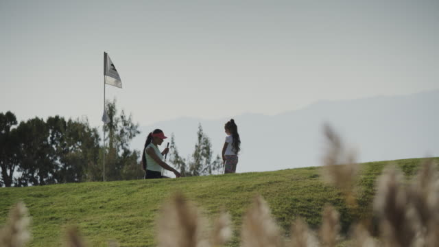 distant woman and girl golfing and high-fiving / cedar hills, utah, united states - golf swing stock videos & royalty-free footage