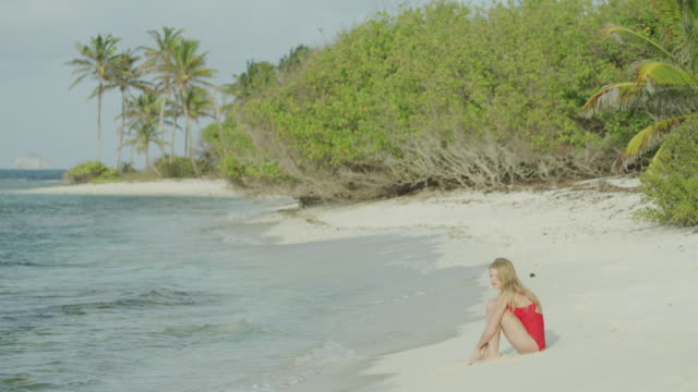 distant woman sitting on beach near ocean waves / petit tabac, tobago cays, st. vincent and the grenadines - ausgefranst stock-videos und b-roll-filmmaterial