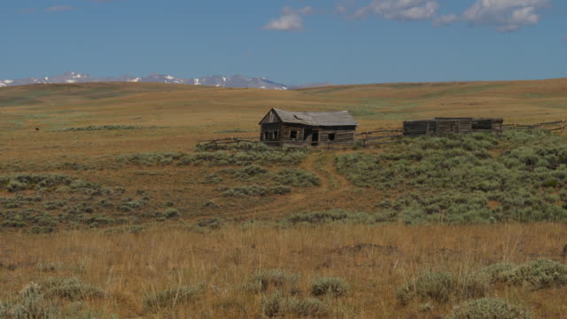 Distant wooden shack in remote landscape / Atlantic City, Wyoming, United States