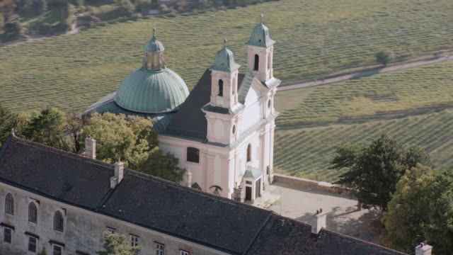 stockvideo's en b-roll-footage met aerial distinctive cathedral and turreted wall set on heavily wooded hilltop, valley and river below - torenspits