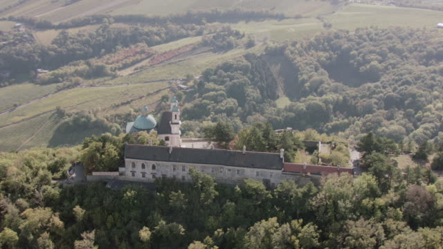 stockvideo's en b-roll-footage met aerial distinctive cathedral and turreted wall set on heavily wooded hilltop, valley, urban space, and river below - torenspits