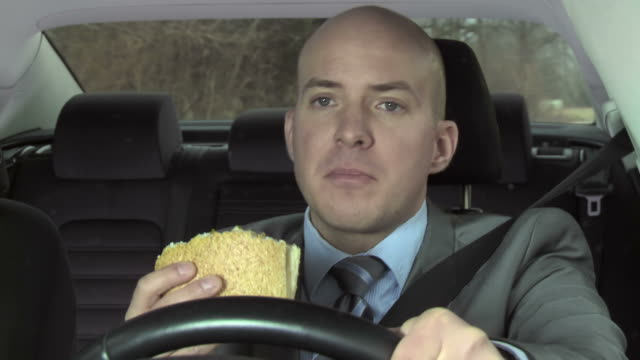 hd: distracted driver eating while driving - car interior stock videos & royalty-free footage