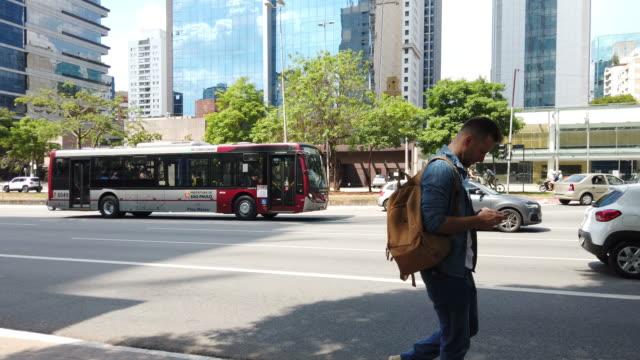 vídeos de stock, filmes e b-roll de homem confundido que anda olhando seu móbil e quase batendo em um borne. - ônibus