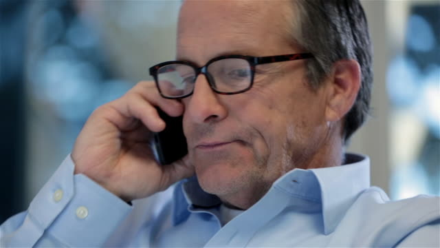 Distracted older businessman talks on smart-phone in private corporate office (dolly shot)