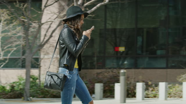 vídeos y material grabado en eventos de stock de distracted woman texting on cell phone walking into post on sidewalk / salt lake city, utah, united states - vista de costado