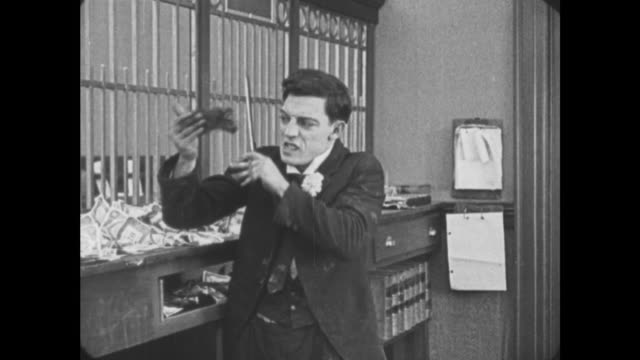 1921 distraught bank teller (buster keaton) glues hand to hair and has to cut it with scissors - 1921 stock videos & royalty-free footage