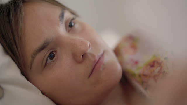 vidéos et rushes de a distraught heartbroken woman reads a breakup letter while lying in bed - être étendu