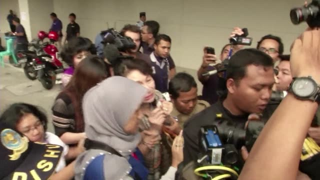 Distraught relatives of passengers onboard the missing AirAsia flight are carried off on stretchers after watching news reports showing debris and...