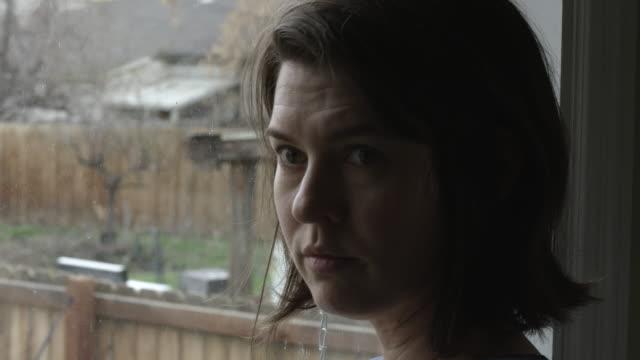 distraught woman standing by window - プロボ点の映像素材/bロール